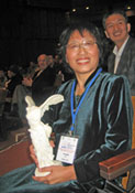 Photo of Dr. Liu Chuang receiving the 2008 CODATA Prize, symbolized by a reproduction of the Louvre's Winged Victory of Samothrace.
