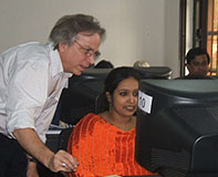 Mark Becker instructs a student in geospatial analysis as she sits at the computer.