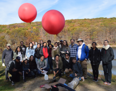 Group of Columbia University GIS students and professors pose with balloons used to aerially collect data on field trip
